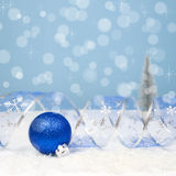 Christmas Decoration with a blue ball, curved ribbon on bokeh ba Stock Images