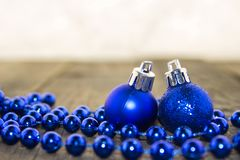 Christmas decorations, silver and blue. Christmas decoration with blue feathers and blue shiny balls on a wooden surface Royalty Free Stock Photography