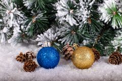 Christmas decoration blue and gold balls in a tree with tinsel and pinecone in snow. Christmas decoration, blue and gold balls in a snowed tree with pinecones stock photos
