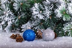 Christmas decoration blue and silver balls in a tree with tinsel and pinecone in snow. Christmas decoration, blue and silver balls in a snowed tree with stock image