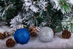 Christmas decoration blue and silver balls in a tree with tinsel and pinecone in snow. Christmas decoration, blue and silver balls in a snowed tree with royalty free stock images