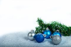 Christmas decoration blue balls and silver and tinsel in a snowed place. Christmas decoration, bluetinsel with blue balls in a snowed table and white backgorund royalty free stock image