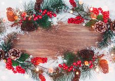 Christmas decoration, branch of fir tree with cones and snow on wooden background. Merry Christmas and Happy New Year theme Royalty Free Stock Photos