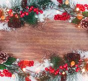Christmas decoration, branch of fir tree with cones and snow on wooden background. Merry Christmas and Happy New Year theme Stock Photos
