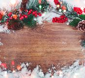 Christmas decoration, branch of fir tree with cones and snow on wooden background. Merry Christmas and Happy New Year theme Royalty Free Stock Image