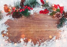 Christmas decoration, branch of fir tree with cones and snow on wooden background.Merry Christmas and Happy New Year theme. Christmas decoration, branch of fir Royalty Free Stock Image