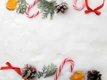 Christmas decoration. Branch tree, cones and candy on snow. Top view, flat lay Royalty Free Stock Images