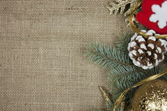 Christmas decoration on burlap texture. Christmas decoration with pine cones, pine branches, red gloves ans golden snow flake on burlap texture stock photos