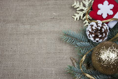 Christmas decoration on burlap texture. Christmas decoration with pine cones, pine branches, red gloves ans golden snow flake on burlap texture royalty free stock photography