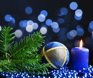 Christmas decoration with burning candle and fir branch. Royalty Free Stock Images