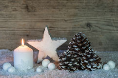 Christmas decoration with burning candle and white wooden star. Royalty Free Stock Photography