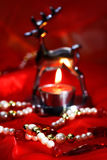 Christmas decoration with burning tea light and beads on red Stock Photography