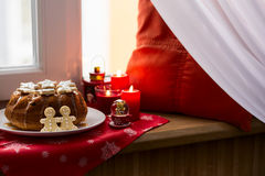 Christmas decoration: cake, gingerbread-men and burning red candles Stock Images