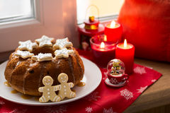 Christmas decoration: cake, gingerbread-men and burning red candles Stock Photography