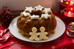 Christmas decoration: cake, gingerbread-men and burning red candles Royalty Free Stock Photography
