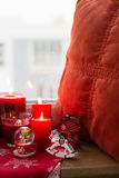 Christmas decoration: candies, toys,pillow and burning red candles Stock Photo