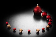 Christmas decoration: candle and balls. Of glass in circle on dark background with light copyspace middle Royalty Free Stock Photography