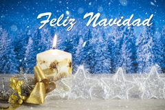 Christmas decoration with candle, golden bow, silver stars, with text in Spanish `Feliz Navidad` in a blue forest background.  royalty free stock images