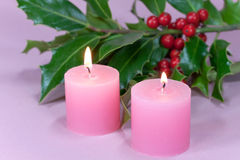 Christmas decoration with candle light,holly. A christmas decoration with candle light,holly leaves and berries Stock Images