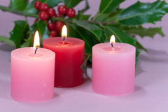 Christmas decoration with candle light,holly. A christmas decoration with candle light,holly leaves and berries Royalty Free Stock Images