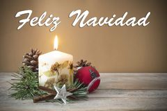 Christmas decoration with candle, pine, bauble, with text in Spanish `Feliz Navidad` in wooden background.  Royalty Free Stock Images