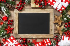 Christmas decoration chalkboard gift box stars red ornaments dar. Christmas decoration with chalkboard, gift box, stars and red ornaments. Dark toned picture royalty free stock photography