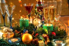 Christmas decoration and champagne. Christmas decoration with baubles,gift,candlelights,green twig,champagne and wine in glasses on golden backgroundwith twinkle Royalty Free Stock Photo