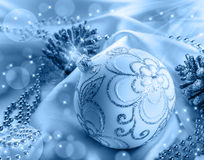 Christmas decoration. Christmas ball, pine cones, glittery jewels on white satin. Stock Image