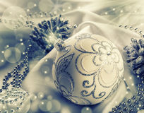 Christmas decoration. Christmas ball, pine cones, glittery jewels on white satin. stock photography