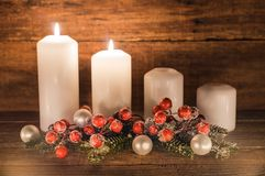 Second Advent. Christmas decoration with christmas bauble, red berries, fir branches and candles for Advent season two candles burning Stock Image