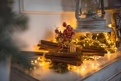 Christmas Decoration, cinnamon sticks in festive lights garland yellow. royalty free stock photography