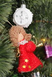 Christmas decoration -clock and red angel. Christmas decoration - glass clock and red angel with musical instrument on christmas tree Stock Photo