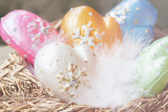 Christmas decoration from colorful decorative celluloid mittens with white bird fluff in nest. Element of Christmas. Christmas decoration from colorful Stock Image