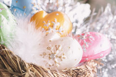Christmas decoration from colorful decorative celluloid mittens with white bird fluff in nest. Element of Christmas. Christmas decoration from colorful Royalty Free Stock Image