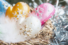 Christmas decoration from colorful decorative celluloid mittens with white bird fluff in nest. Element of Christmas design, holiday decorations Stock Photos