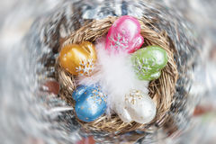 Christmas decoration from colorful decorative celluloid mittens with white bird fluff in nest. Element of Christmas design, holiday decorations Stock Photo