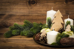 Christmas decoration - compoition from candles, branches, stones on the wooden background. Christmas decoration - compoition from candles, branches and stones Stock Photos