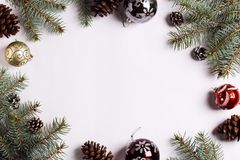 Christmas decoration composition pine cones balls spruce branches on white festive table. New year winter holiday xmas. Top view flat lay copy space Royalty Free Stock Image