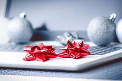 Christmas decoration on a computer. Laptop on a wooden table and white wall. Business concept during a holiday. Xmas concept. Christmas decoration on a computer stock photos