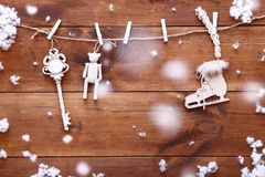 Christmas decoration concept, white toys hanging on brown wooden background with snow, winter holidays card, top view Royalty Free Stock Photography
