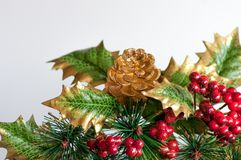 Holly and fircone. Christmas decoration consisting of artificial golden fir cone and holly with red berries. White background Stock Images
