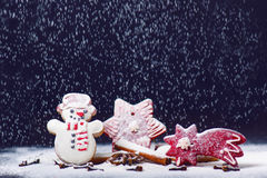 Christmas decoration and cookies.Woman hand sprinkling sugar on a cookies. Flour and spices for a baking on a dark backg Stock Image