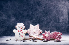 Christmas decoration and cookies.Woman hand sprinkling sugar on a cookies. Flour and spices for a baking on a dark backg Stock Photos