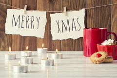 Christmas decoration. Christmas cozy scene: candles, a red mug and a bowl with some shortbread on a white wooden table. Merry xmas is hanging on a rope with Stock Photo