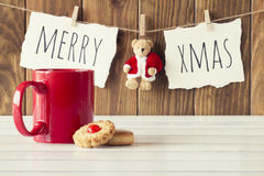 Christmas decoration. Christmas cozy scene: a red mug and some shortbread on a white wooden table. Merry xmas and a Teddy bear with Santa Claus dress is hanging Royalty Free Stock Image