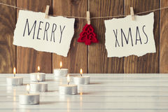 Christmas decoration. Christmas cozy scene: some candles on a white wooden table. Merry xmas and a felt tree is hanging on a rope with clothespins. Vintage Style Stock Photos