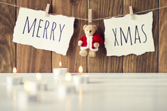 Christmas decoration. Christmas cozy scene: some candles on a white wooden table. Merry xmas and a Teddy bear with Santa Claus dress is hanging on a rope with Stock Photos