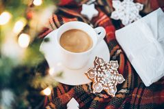 Christmas decoration with a cup of coffee, gingerbread and plaid. Blanket, new year lights bokeh closeup Stock Images