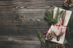 Christmas decoration with cutlery and napkin on the wooden table, top view. Copy space.  Royalty Free Stock Photo