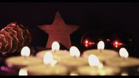 Soft focus shift from burning candles to star. Christmas decoration on dark background with  burning candles in front to wooden star in the back stock video